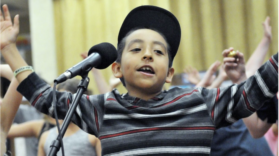 Child in front of a microphone cheering