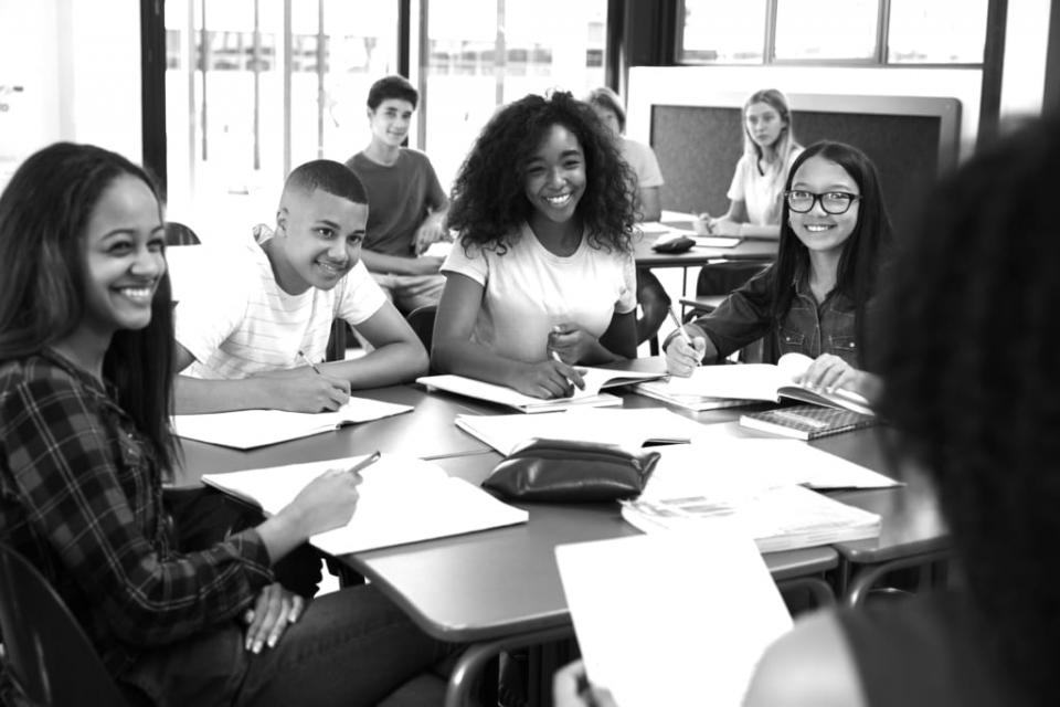 Black and white picture of students surrounding a table smiling