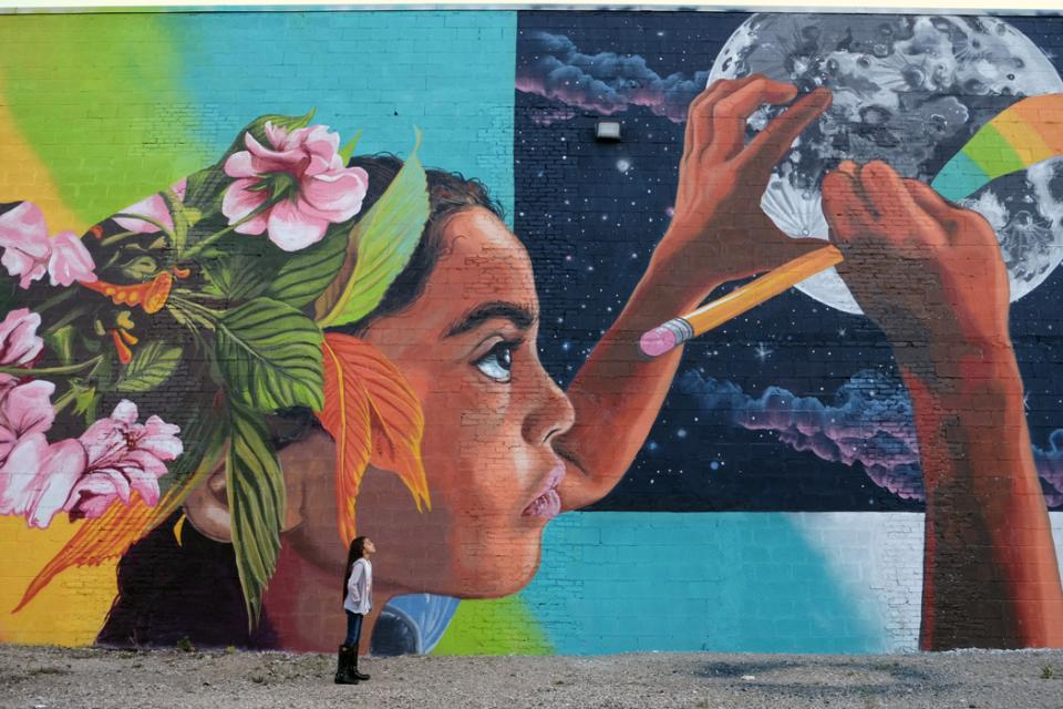 Young girl looking at a mural of a young girl